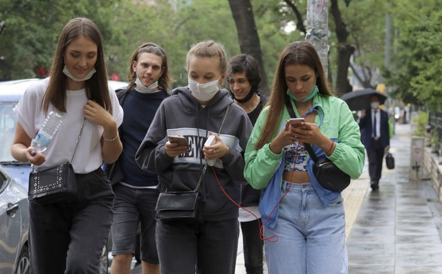 People walk in a popular street, in Ankara, Turkey, Wednesday, June 17, 2020. Turkey has made the wearing of face masks mandatory in five more provinces, following an uptick in COVID-19 cases. Health Minister Fahrettin Koca tweeted Tuesday that the wearing of masks is now compulsory in 42 of Turkey's 81 provinces. (Photo by Burhan Ozbilici/AP Photo)