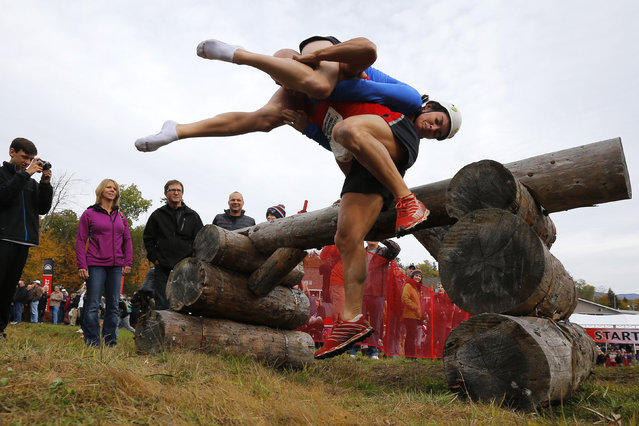 Jeff and Kelly Lyons clear the first obstacle while competing in the North American Wife Carrying Championship at Sunday River ski resort in Newry, Maine October 11, 2014. REUTERS/Brian Snyder