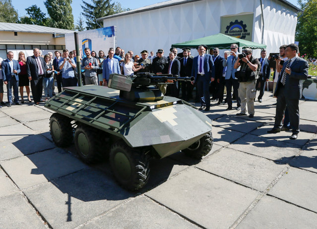 Journalists and officials gather around a remotely controlled military vehicle during a presentation at the Kiev armoured plant, Ukraine August 29, 2016. (Photo by Valentyn Ogirenko/Reuters)
