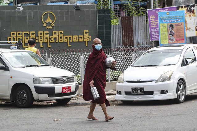 A Buddhist monk wearing face mask to help curb the spread of the new coronavirus, walks to collect morning alms from devotees in Yangon, Myanmar Monday, May 18, 2020. (Photo by Thein Zaw/AP Photo)
