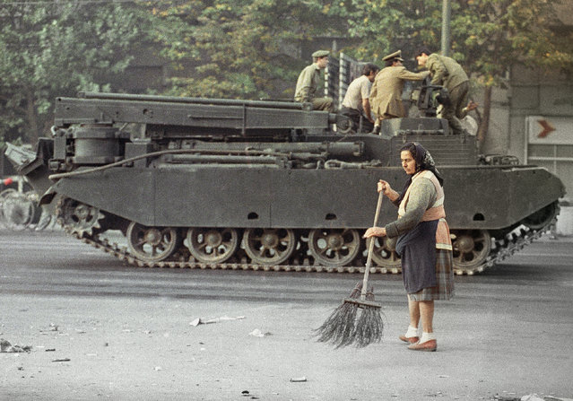 A woman sweeps a street in Bucharest's University Square, Saturday, September 28, 1991 as an armored vehicle rumbles by. Government security forces secured the center of Bucharest and dismantled barricades erected by miners during three days of anti-government rioting. (Photo by Steven Senne/AP Photo)