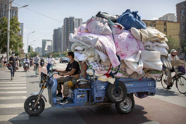 A man wearing a face mask to protect against the new coronavirus drives a cart loaded with fabric in Beijing, Tuesday, July 14, 2020. Health experts are warning that outbreaks brought under control with shutdowns and other forms of social distancing are likely to flare again as precautions are relaxed.(Photo by Mark Schiefelbein/AP Photo)
