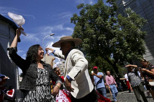 A voter in traditional huaso dress dances with an election worker in front of a polling station center after he voted in the  presidential elections runoff in Santiago, Chile, Sunday, December 17, 2017. Chileans voters will decide Sunday whether to swing the world's top copper-producing country to the right or maintain its center-left path in a fiercely contested presidential runoff election. (Photo by Esteban Felix/AP Photo)