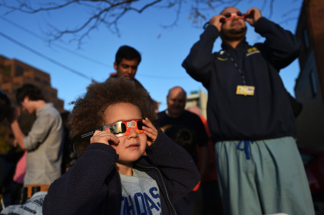 Bennie Thomas, 4, of Ann Arbor holds a pair of special glasses up so that he can view a partial solar eclipse with his father Jared, at right, along S. Ashley St. in Ann Arbor, Mich., on Thursday, October 23, 2014. Members of the University Lowbrow Astronomers set up several telescopes available for the public to use. (Photo by Melanie Maxwell/AP Photo/The Ann Arbor News)