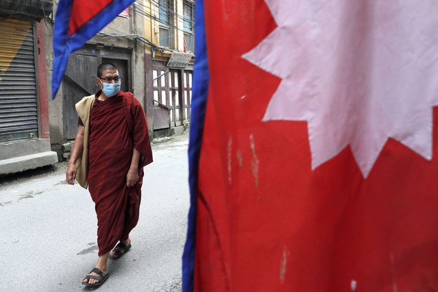 A Nepalese Buddhist monk wearing face mask walks past a Nepalese flag displayed outside a curio shop in Kathmandu, Nepal, Wednesday, July 22, 2020. Nepal's government has ended a lockdown 120 days after it was imposed to control the spread of coronavirus. (Photo by Niranjan Shrestha/AP Photo)