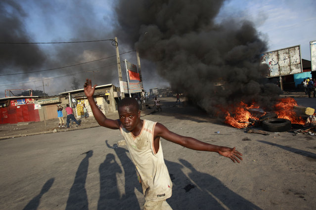 Supporters of opposition leader Alassane Ouattara burn tires in protest following the results of the election, in the Marcory neighborhood of Abidjan, Ivory Coast, Friday, December 3, 2010. (Photo by Rebecca Blackwell/AP Photo)