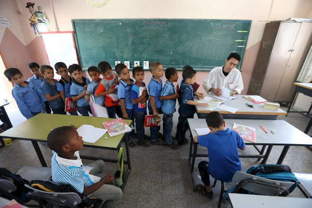 Mohammed Zurob marks an exercise for his first grade students during an English lesson inside a classroom at Taha Huseen elementary school in Rafah in the southern Gaza Strip September 28, 2015. (Photo by Ibraheem Abu Mustafa/Reuters)