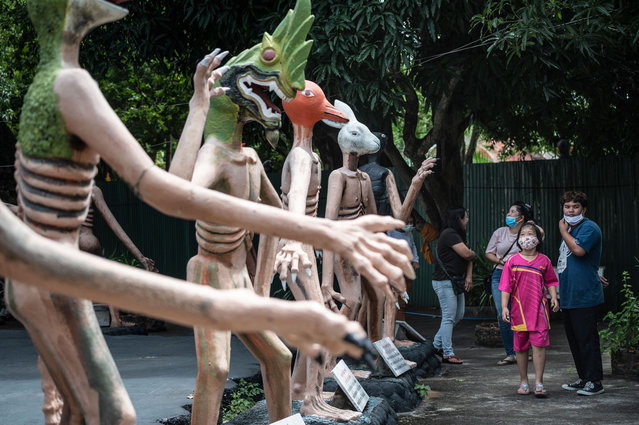 Visitors look at statues illustrating the fate of people who do bad deeds in a garden depicting a Buddhist version of hell at the Wat Saeng Suk temple in the Thai coastal province of Chonburi on July 9, 2020. (Photo by Lillian Suwanrumpha/AFP Photo)