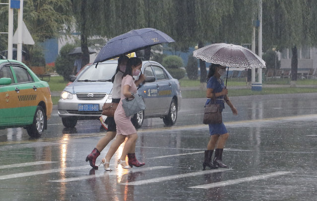Women walk with umbrellas during torrential rains, Wednesday, August 5, 2020, in Pyongyang. North Korea says torrential rains have lashed the country, prompting outside worries about possible big damages in the impoverished country. (Photo by Cha Song Ho/AP Photo)