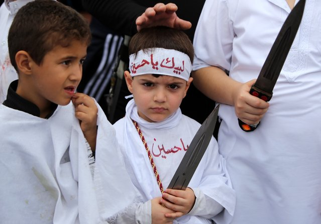 Iraqi Shiite boys take part in a self-flagellation ceremony during a parade ahead of Ashura in Baghdad's northern district of Kadhimiya on November 3, 2014. Iraq has implemented heavy security measures involving tens of thousands of security forces members and allied militiamen to protect Shiites during Ashura. Hundreds of thousands of Shiites will flock to the shrine city of Karbala south of Baghdad for Ashura, which marks the death of Imam Hussein, one of the most revered figures in Shiite Islam. (Photo by Ahmad Al-Rubaye/AFP Photo)