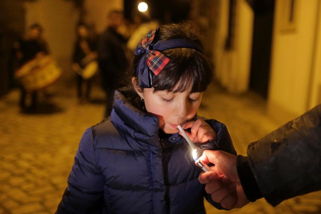An adult helps a young girl light a cigarette as a band plays in the background in the village of Vale de Salgueiro, northern Portugal, during the local Kings' Feast Friday, January 5, 2018. (Photo by Armando Franca/AP Photo)