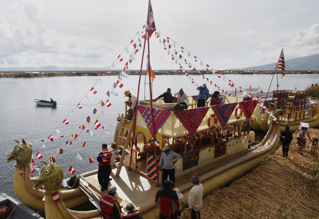 Andeans prepare a totora raft at the shores of a Uros island at Lake Titicaca before a re-enactment of the legend of Manco Capac and Mama Ocllo in Puno November 5, 2014. (Photo by Enrique Castro-Mendivil/Reuters)