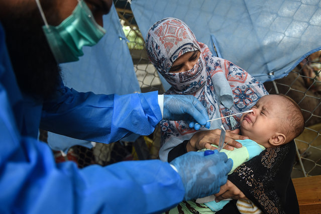 In this picture taken on September 1, 2020, a health official takes a swab sample from a child to test for the COVID-19 coronavirus at a testing site in Karachi. Six months after the coronavirus arrived in Pakistan, the country appears to have dodged the worst of the pandemic, baffling public health experts and dampening fears its crowded urban areas and ramshackle hospitals will be overrun. (Photo by Rizwan Tabassum/AFP Photo)