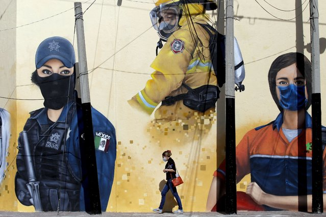 "A women walks in front of a mural, painted by workers of the Zapopan city hall as part of the program ""Zapopart"", as a tribute to essential workers who have cared for citizens during the COVID-19 pandemic in Zapopan, state of Jalisco, Mexico, on August 12, 2020, amid the novel coronavirus pandemic. (Photo by Ulises Ruiz/AFP Photo)"