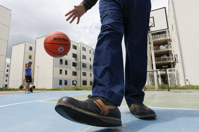 Jeison Rodriguez, 19, the living person with the largest feet in the world, plays basketball in front of his house in Maracay, Venezuela, October 14, 2015. (Photo by Carlos Garcia Rawlins/Reuters)