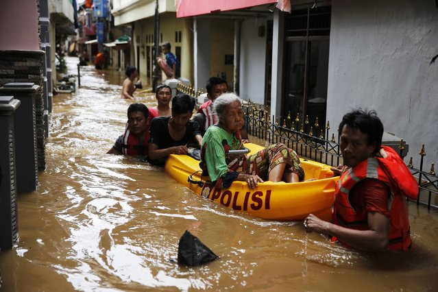 Volunteers use a paddle raft to move an elderly woman to a safe place at Jatinegara district in Jakarta November 20, 2014. Heavy rain caused flooding in some parts of the capital. (Photo by Reuters/Beawiharta)