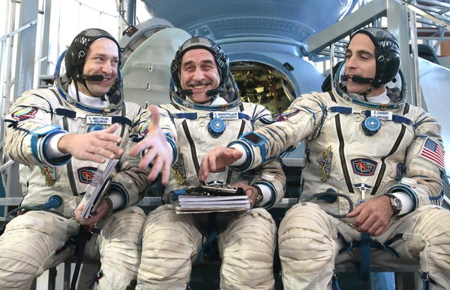 Members of the next expedition to the International Space Station, Russian Cosmonauts Alexander Misurkin, left, and Pavel Vinogradov, center, and US astronaut Christopher Cassidy prepare to shake hands before their final preflight practical examination in a mock-up of a Soyuz TMA space craft at Russian Space Training Center in Star City outside Moscow, Russia, Tuesday, March 5, 2013. The three are the next crew scheduled to blast off to the International Space Station from Baikonur cosmodrom on a Russian made Soyuz TMA-08M space craft on March 28. (Photo by Mikhail Metzel/AP Photo)