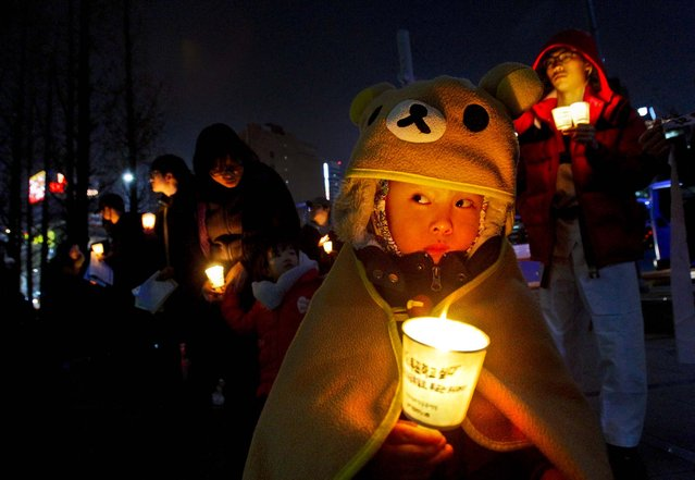 A child holds a candle during a rally denouncing the annual joint military exercises between South Korea and the United States in Seoul, South Korea, on March 15, 2013. (Photo by Ahn Young-joon/Associated Press)
