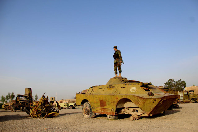An Afghan soldier stands in a junkyard of Soviet-era tanks on the 29th anniversary of Soviet-Afghan War, in Kandahar, Afghanistan, 15 February 2018. Between 25 December 1979 and 15 February 1989, a total of 620,000 Soviet Union soldiers and other security personnel served in Afghanistan. Fatal casualties came to 14,453. (Photo by Muhammad Sadiq/EPA/EFE)
