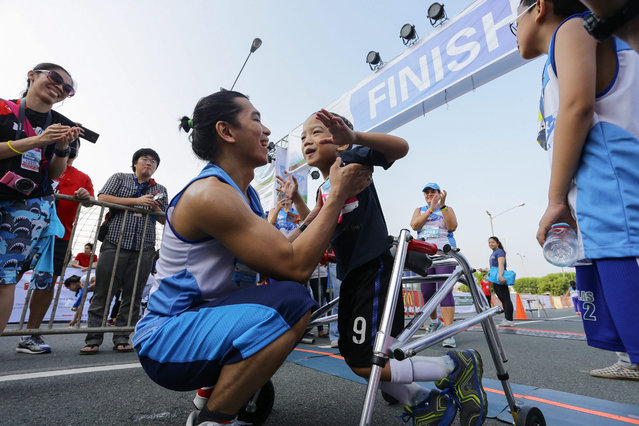 A Filipino child with disability, Niah Villamar (C-R) celebrates with his father, Lem (C-L) as they cross the finish line at the 'Heroes for Children Run' in Pasay City, south of Manila, Philippines, 25 October 2015. According to UNICEF, an estimate of three thousand participants, including persons with disabilities (PWD's) and children attended the sports event aimed to raise funds for UNICEF's 1,000 Days campaign. (Photo by Mark R. Cristino/EPA)