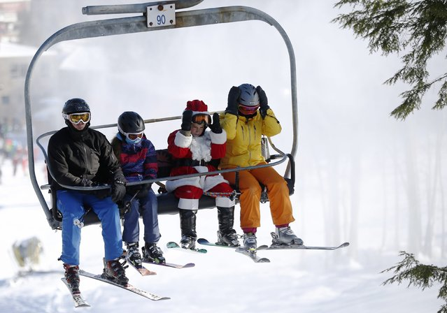 A skier dressed as Santa Claus rides a lift after participating in a charity run down a slope at Sunday River Ski Resort in Newry, Maine December 7, 2014. (Photo by Brian Snyder/Reuters)