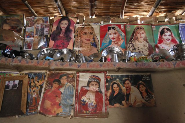 Utensils placed on a mud wall shelf adorned with Bollywood film star posters are seen in a room owned by a cotton picker's family in Meeran Pur village, north of Karachi November 23, 2014. (Photo by Akhtar Soomro/Reuters)
