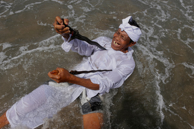 A Balinese Hindu worshiper attempts to stab himself with traditional Kris daggers while in trance during Melasti, a purification ceremony ahead of the holy day of Nyepi on a beach in Gianyar, Bali, Indonesia  March 14, 2018. (Photo by Johannes P. Christo/Reuters)