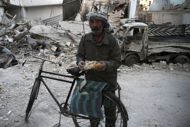 A man carries a corn comb in a damaged site after an airstrike yesterday in the rebel held Douma neighbourhood of Damascus, Syria October 4, 2016. (Photo by Bassam Khabieh/Reuters)