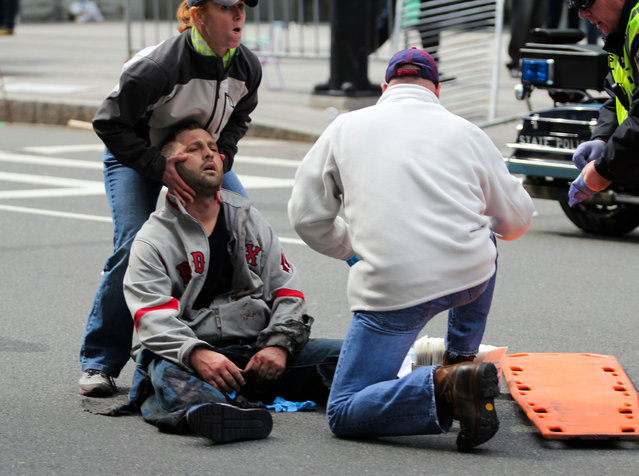 In this photo provided by The Daily Free Press and Kenshin Okubo, people assist an injured after an explosion at the 2013 Boston Marathon in Boston, Monday, April 15, 2013. (Photo by Kenshin Okubo/AP Photo/The Daily Free Press)
