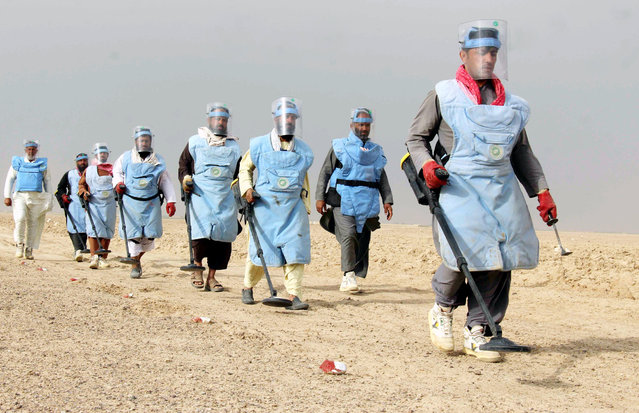 Afghan workers preapre to search for landmines in Kandahar, Afghanistan, 19 March 2018. Several workers belonging to different Government and Non-Government organizations have been cleaning the volatile southern part of the country from landmines that have been planted during the Soviet War. (Photo by Muhammad Sadiq/AFP Photo)