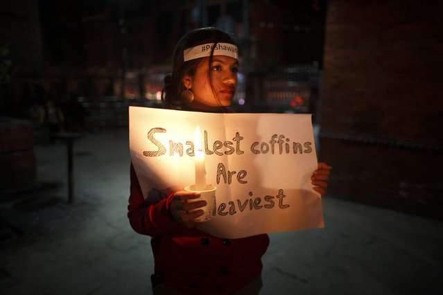 A woman holds a placard and a candle as she attends a candle light vigil in Kathmandu December 17, 2014, for the students killed at the military-run Army Public School in Peshawar. Pakistan woke up to a day of mourning on Wednesday after Taliban militants killed 132 students in a grisly attack which shocked the nation and put pressure on the government to do more to tackle the insurgency. (Photo by Navesh Chitrakar/Reuters)