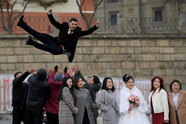 Newlyweds celebrate their wedding surrounded by friends on Red Square in Moscow on November 11, 2020, amid the ongoing coronavirus disease pandemic. (Photo by Natalia Kolesnikova/AFP Photo)