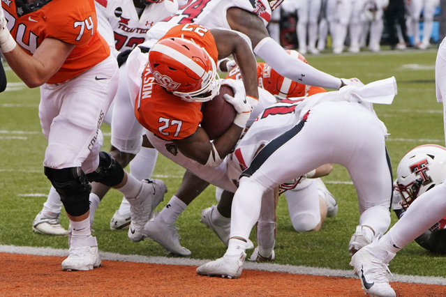 Oklahoma State running back Dezmon Jackson (27) scores against Texas Tech in the first half of an NCAA college football game in Stillwater, Okla., Saturday, November 28, 2020. (Photo by Sue Ogrocki/AP Photo)