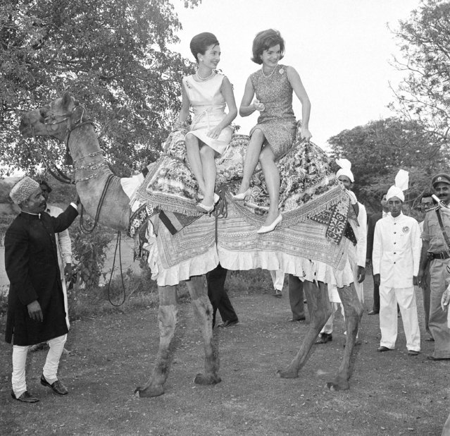 Mrs. Jacqueline Kennedy, the widely traveled wife of Pres. John F. Kennedy, right, perches on camel with her is her sister, Princess Lee Radziwill March 1, 1962, Karachi, Pakistan. Mrs. Kennedy was on a goodwill visit to India and Pakistan. Holding the camel is Bashir Ahmad, left, who won fame when he came to the U.S. last year as a guest of Vice Pres. Lyndon Johnson. (Photo by AP Photo)