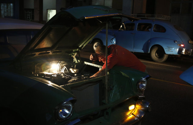 In this December 20, 2014 photo, a taxi driver repairs his vintage American car in Havana, Cuba. U.S. car sales have been banned in Cuba since 1959. Cubans have been have been forced to patch together Fords, Chevrolets and Chryslers that date back to before Fidel Castro's revolution which can make it appear like the country is stuck in a 1950s time warp. (Photo by Desmond Boylan/AP Photo)