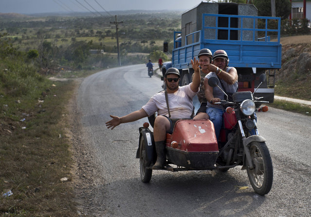 "In this April 13, 2018 photo, motorcycle taxi driver Ricardo Medina, 60, transports vegetable vender Rigoberto Herrera Mendez, left, and coconut vendor Osvaldo Ochoa in Campo Florido, east of Havana, Cuba. The three men expressed hope that new government leadership will improve things, saying the country cannot move backwards. ""We survive life with our work"", said Medina. (Photo by Ramon Espinosa/AP Photo)"