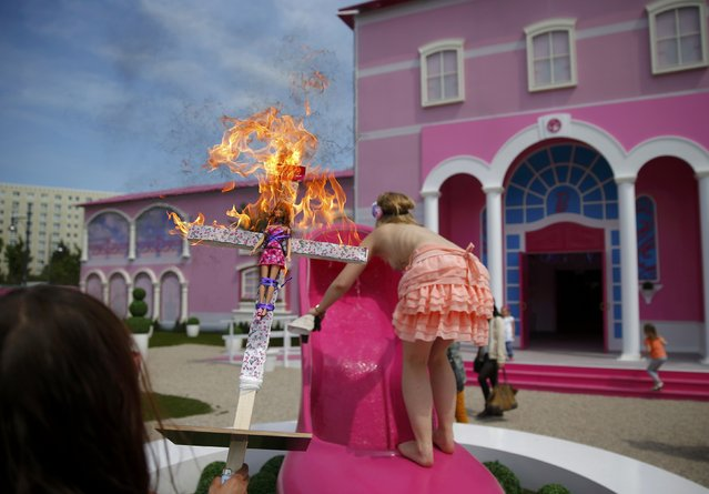 """Activists from women's rights group Femen burn a barbie doll on a cross as they protest outside a """"Barbie Dreamhouse"""" of Mattel's Barbie dolls in Berlin, May 16, 2013. (Photo by Pawel Kopczynski/Reuters)"""