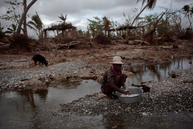 A woman does her laundry on a beach after Hurricane Matthew in Les Cayes, Haiti, October 20, 2016. (Photo by Andres Martinez Casares/Reuters)