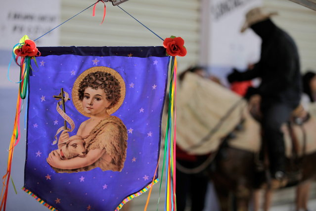 """A banner of St John the Baptist hangs from the storefront of an artisan shop in Pirenopolis, Brazil, during the annual """"Cavalhadas"""" festival, Sunday, May 19, 2013. The popular festival, featuring masked horsemen, is a tradition that was introduced in the 1800's by a Portuguese priest to mark the the ascension of Christ. The 3-day festival reenacts the Christian knights' medieval defeat of the Moors. (Photo by Eraldo Peres/AP Photo)"""