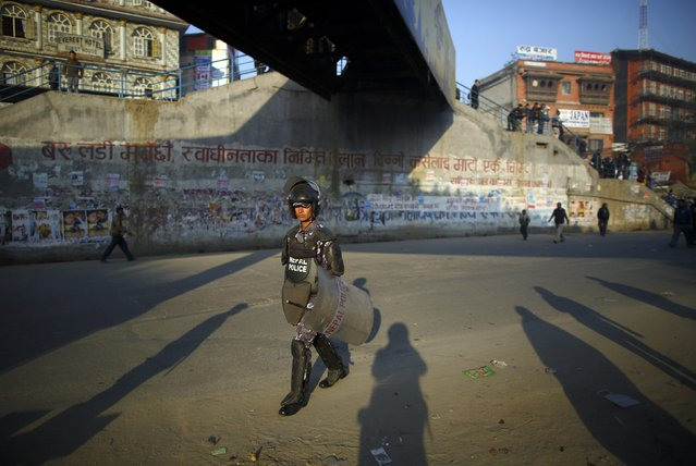 A Nepalese police personnel stands guard near protesters (unseen) during the general strike independently called by the Unified Communist Party of Nepal (Maoist) and led by 30 party alliance and the Communist Party of Nepal (Maoist), demanding that the drafting of the new constitution is done on time through consensus, in Kathmandu January 13, 2015. (Photo by Navesh Chitrakar/Reuters)