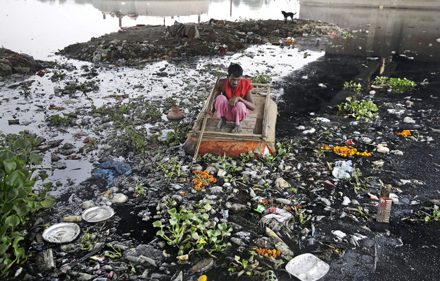 In this photo taken May 28, 2018, Ram Nath, 40, who makes a living from recycling trash, rummages for plastic bottles and other reusable trash while rowing a makeshift boat through murky waters of Yamuna, India's sacred river that flows through the capital of New Delhi. India produces more than 68 million tons of trash every day. More than 17,000 tons of it is plastic. That requires immense dumps, which in cities like New Delhi, mean hills of stinking trash up to 50 meters tall. Last year, two people were killed when a large part of one of the city's dumps crashed down onto them. (Photo by Altaf Qadri/AP Photo)