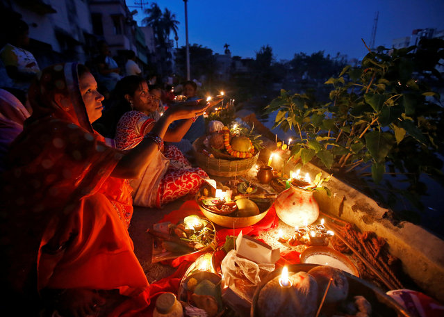 Hindu devotees hold earthen lamps as they worship the rising sun at the corner of a pond during the religious festival of Chhat Puja in Kolkata, November 7, 2016. (Photo by Rupak De Chowdhuri/Reuters)