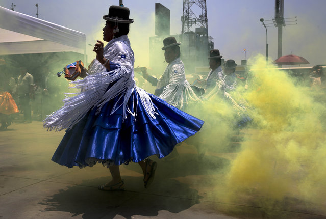 Dancers wearing bowler hats perform in a cloud of theatrical smoke in a pre-feast presentation in honor of Our Lady of Candelaria's upcoming feast day celebrations, in Lima, Peru, Thursday, January 22, 2015. A 15-day festival takes place annually in the patron saint's honor in Puno, over 800 miles southeast of Lima. The cultural event, which begins Feb. 1, is recognized as one of the most popular and significant in South America. (Photo by Martin Mejia/AP Photo)
