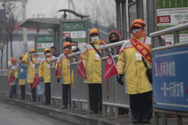 "Traffic assisting coordinators wearing masks work at a bus station amid heavy smog after the city issued its first ever ""red alert"" for air pollution, in Beijing, China, December 9, 2015. (Photo by Reuters/China Daily)"