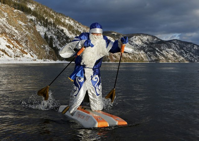 Nikolai Vasilyev, 62, dressed as Father Frost, Russian equivalent of Santa Claus, water-skis along the Yenisei River outside Siberian city of Krasnoyarsk, Russia, December 10, 2015. Vasilyev, a teacher of the Krasnoyarsk Aerospace Academy, constructed the self-made water skis to travel on the water surface. The skis are made of plastic foam and the sticks are designed to propel him forward. (Photo by Ilya Naymushin/Reuters)