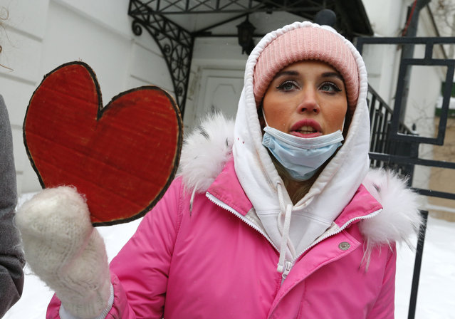 A woman, wearing face masks to protect against coronavirus, attends a rally in support of jailed opposition leader Alexei Navalny and his wife Yulia Navalnaya, in Moscow, Russia, Sunday, February 14, 2021. (Photo by Alexander Zemlianichenko/AP Photo)