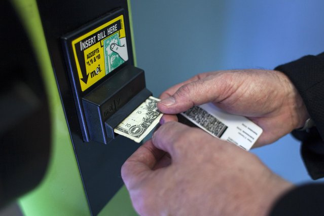 Stephen Shearin inserts a note as he demonstrates the use of a ZaZZZ vending machine that contains cannabis flower, hemp-oil energy drinks, and other merchandise at Seattle Caregivers, a medical marijuana dispensary, in Seattle, Washington February 3, 2015. (Photo by David Ryder/Reuters)