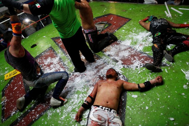 Wrestler known as Ciclope (C) lies on the floor after losing an extreme wrestling fight against Los Malkriados at a temporary wrestling ring inside a car wash in Tulancingo Hidalgo, Mexico October 8, 2016. (Photo by Carlos Jasso/Reuters)
