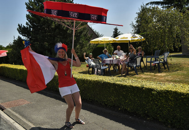 A spectator waves the French flag from the side of the route at the start of the ninth stage of the 105th edition of the Tour de France cycling race between Arras and Roubaix, northern France, on July 15, 2018. (Photo by Marco Bertorello/AFP Photo)