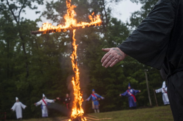 A tattoo on the knuckles of a Klansman reads Love as he participates with members of the Nordic Order Knights and the Rebel Brigade Knights, groups that both claim affiliation with the Ku Klux Klan, in a cross lighting ceremony on a fellow member's property in Henry County, Virginia, August 9, 2014. The Ku Klux Klan, which had about 6 million members in the 1920s, now has some 2,000 to 3,000 members nationally in about 72 chapters, or klaverns, according to the Southern Poverty Law Center, an organization that monitors extremist groups. (Photo by Johnny Milano/Reuters)